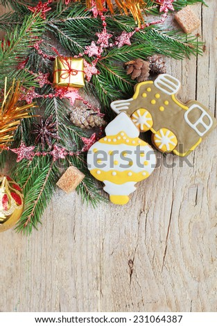 Homemade christmas gingerbreads painted as a yellow white Christmas tree toy and a train with festive decoration on the wooden background with fir branches. Selective focus and place for text. - stock photo