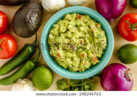 Homemade chunky guacamole in bright blue bowl surrounded by dip ingredients - stock photo