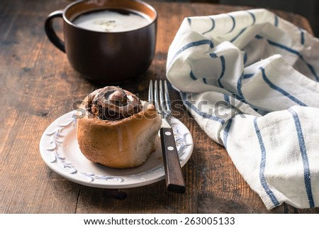 Homemade cinnamon bun with chocolate and light glaze on white plate with fork. Cup of coffee and white napkin on side, rustic wooden table background. Breakfast image, warm earthy tones - stock photo