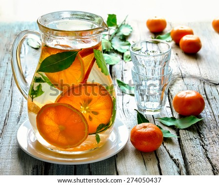 Homemade citrus infused water in a jug on a rustic background in a sunny day - stock photo