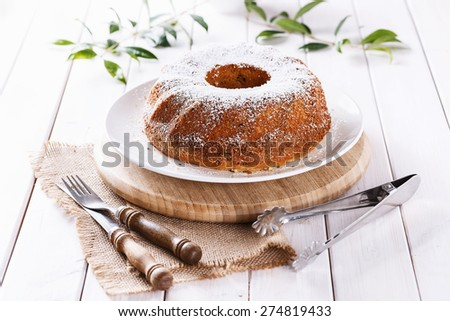 Homemade classic Bundt Cake dusted with icing sugar on a white plate over white wooden background. Close up, Selective focus - stock photo