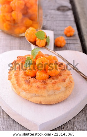 homemade coconut cookies with jam and fresh berries of cloudberries on a wooden background - stock photo