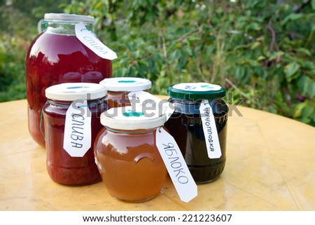 homemade compote and jam pots with Russian labels on the table on orchard background - stock photo