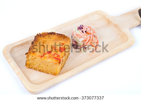 Homemade Cornbread cut into squares and salad on wood plate with - stock photo
