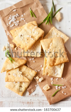 Homemade crackers with rosemary and sea salt for appetizer on an old cooking board. - stock photo