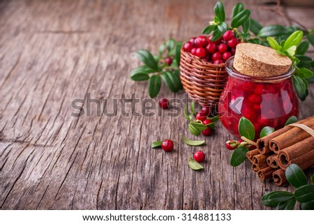 Homemade cranberry sauce with fresh berries and cinnamon in a small glass jar on a dark wooden background. selective Focus - stock photo
