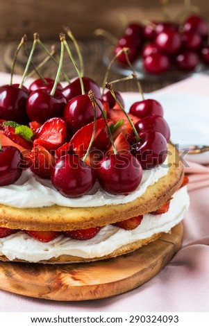 Homemade cream layer cake, fresh, colorful, and delicious dessert with juicy strawberries, sweet cherry, and whipped cream - stock photo