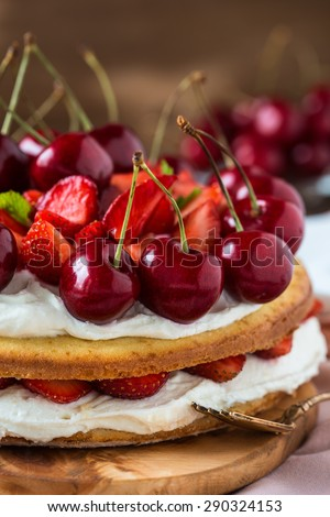 Homemade cream layer cake, fresh, colorful, and delicious dessert with juicy strawberries, sweet cherry, whipped cream and cream cheese - stock photo