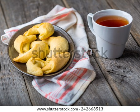 homemade croissants and cup of tea on wooden table - stock photo