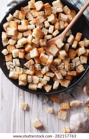 Homemade delicious croutons with garlic on a plate close-up. vertical top view  - stock photo