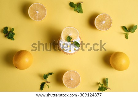 Homemade delicious lemon cupcake with whipped cream topping view from the top. - stock photo