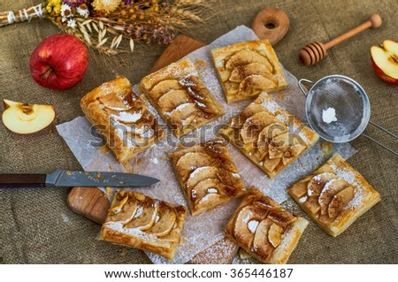 Homemade desserts. A composition with slices of appetizing pie, apples and herbs. Burlap background/Pieces of apple pie - stock photo
