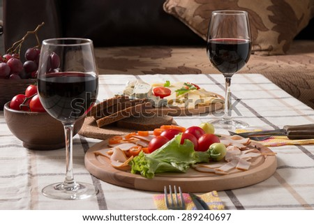 Homemade dinner with bread, tomatoes, cheese, ham and wine on the table - stock photo