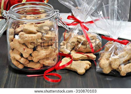 Homemade dog bones being packaged into cellophane bags as healthy gifts for dogs.  Selective focus on foreground cookies. - stock photo
