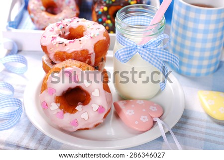homemade donuts with icing glaze and colorful sugar sprinkles and milk in bottle  - stock photo