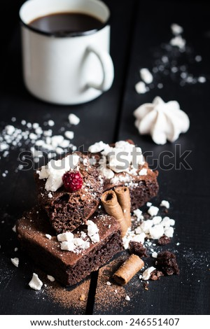 Homemade Double Chocolate Cake with Crushed Meringues, Wafer Rolls, a Ripe Berry on Top and Coffee. Dark Wooden Table Background. Moody Atmosphere - stock photo