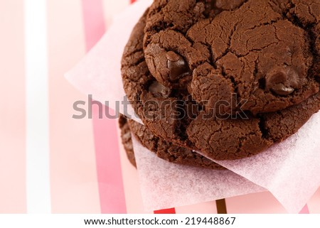 Homemade Double Dark Chocolate cookies on striped background. - stock photo
