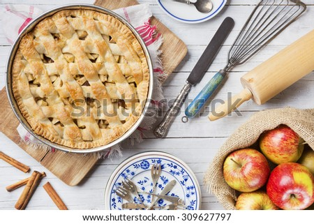 Homemade Dutch apple pie and ingredients on a rustic table. Photographed from directly above. - stock photo