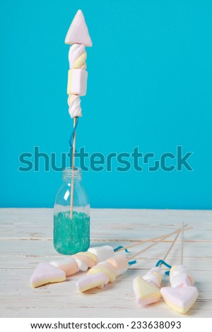 Homemade edible fireworks party favors in the shape of rockets made from colorful marshmallows, on a rustic wooden table against a blue background with copyspace - stock photo