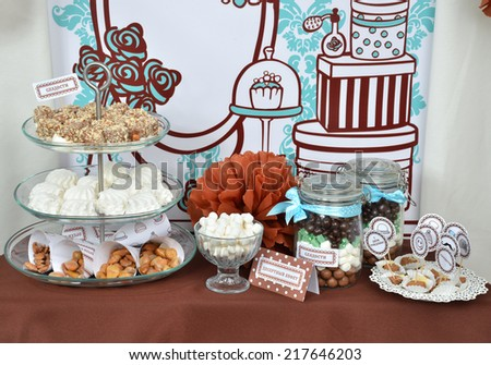 Homemade fancy set table with sweets candies, cake, marshmallows, zephyr, nuts, almonds, truffle as a present for birthday party - stock photo