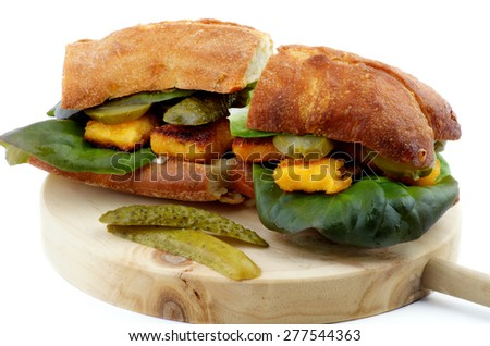 Homemade Fish Burgers with White Fish Sticks, Lettuce, Gherkins and Whole Wheat Bread on Circle Wooden Cutting Board isolated on white background - stock photo