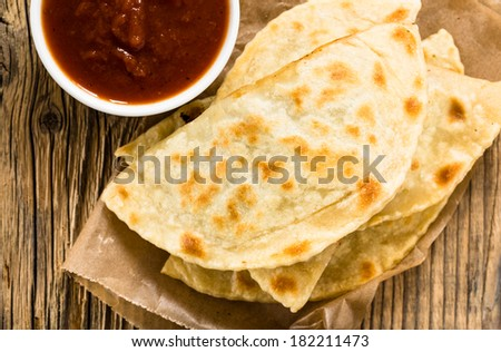 Homemade flatbread with meat, cheese, and salsa viewed from above. Yantyk - traditional Crimean tatar flat bread - stock photo