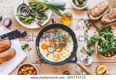 Homemade food background. Include pan with fried seasonal eggs, bowls wits olives, green salad leaves, whole bread baguette and plate fried peppers from above on wooden table. Rustic style. - stock photo