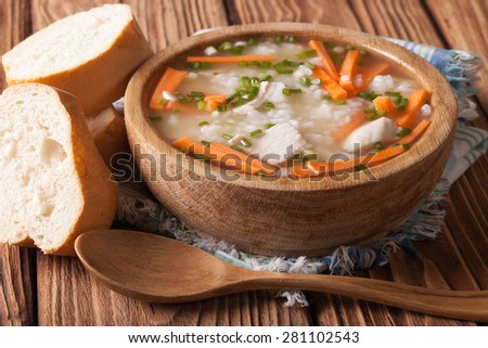 Homemade Food: Chicken rice soup close up in a wooden bowl. Horizontal