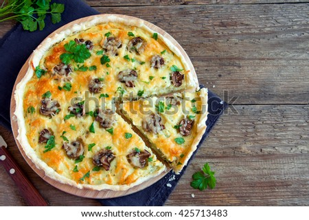 Homemade french quiche pie with mushrooms (champignons) and cheese over rustic wooden background with copy space - stock photo