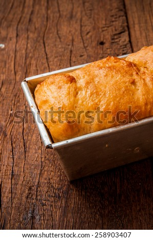 Homemade Fresh Baked Bread from Oven in Square Steel Tin Pan On Wood Table Background, Vintage Rustic Still Life Style / Concept and Idea of Breakfast, Food, Bakery, Dessert Pastry. Close up. - stock photo