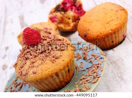 Homemade fresh baked muffins with raspberries and grated chocolate on plate, old rustic wooden background, delicious dessert - stock photo