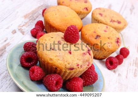 Homemade fresh baked muffins with raspberries on old rustic wooden background, delicious dessert - stock photo