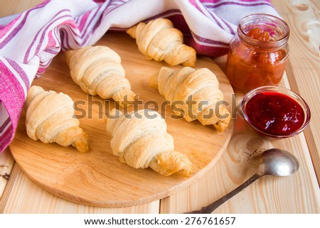 Homemade fresh croissants with jam (marmalade) on wooden table - stock photo