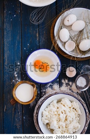 Homemade fresh ricotta cottage cheese made from milk with eggs and jug of milk over on blue wooden table. Rustic style - stock photo