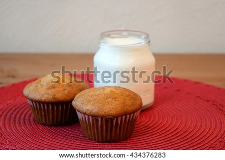 Homemade fresh ripe banana muffins with a glass of milk on red mat and wooden table with white wall background - stock photo