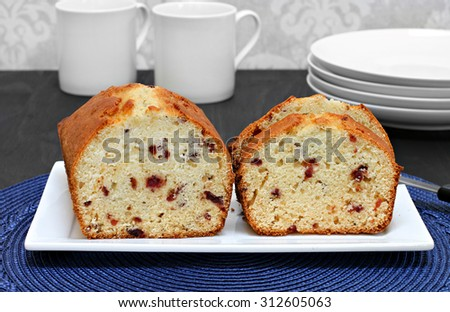Homemade, freshly baked cranberry pound cake on a plate.  Whole portion and sliced pieces. - stock photo