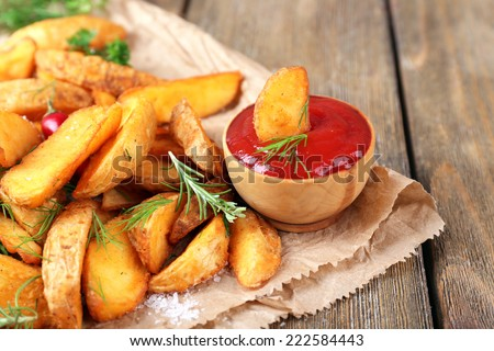 Homemade fried potato with spices and herbs on paper bag, on wooden background - stock photo
