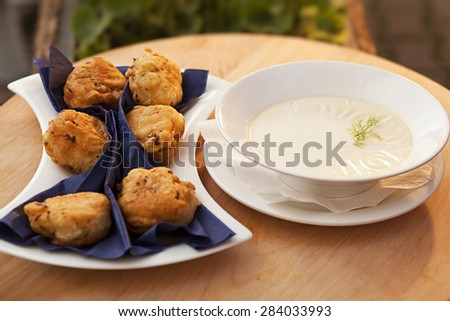 Homemade fritters and cream on wood table - stock photo