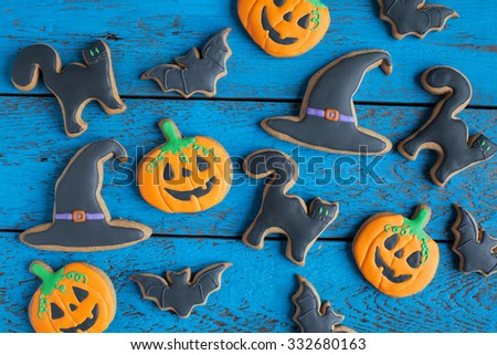 Homemade gingerbread cookies in the form as Halloween jack-o-lantern pumpkins and bats, cats and witch hat on the wooden table. Selective focus.  - stock photo