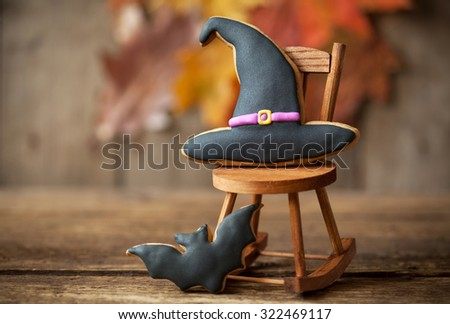 Homemade gingerbread cookies in the form of a halloween witch hat and a bat on a autumn background. Space for text and selective focus on the hat. - stock photo
