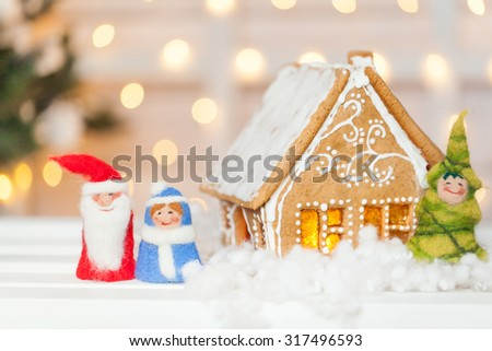 Homemade gingerbread house with felt Santa Claus, Snow-maiden and Christmas tree - stock photo
