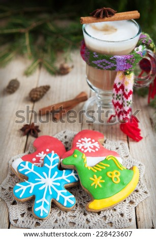 Homemade gingerbreads in the form of a snowflake and a green horse on a wooden table and a glass of warm cacao with a small knit scarf. Selective Focus on gingerbreads. Toned - stock photo