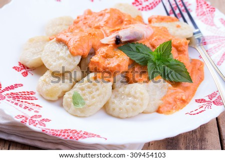 Homemade gnocchi with tomato sauce, shrimp, mint and basil on a tablecloth - stock photo