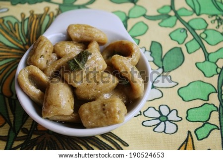 Homemade gnocchi with whole wheat flour served with olive oil and sage - stock photo