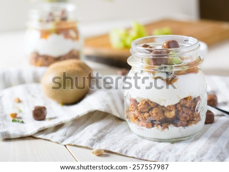 Homemade granola with greak yogurt with kiwi in a glass jar - stock photo
