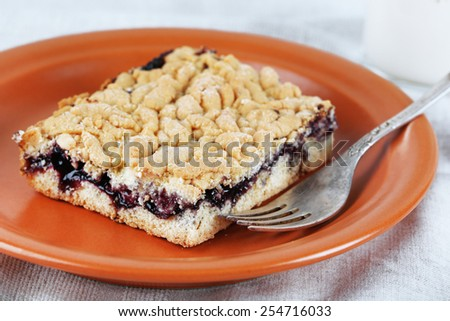 Homemade grated pie with jam and glass of milk on tablecloth background - stock photo