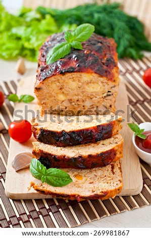 Homemade ground meatloaf with ketchup and basil - stock photo