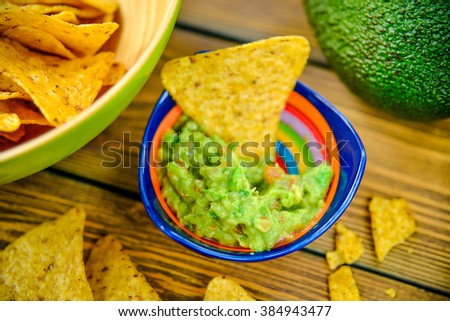 Homemade guacamole with corn chips on rustic wooden table - stock photo
