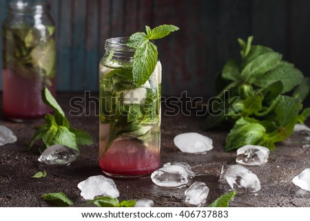 Homemade guava mojito with fresh mint, lime juice and ice on the old dark blue background - stock photo