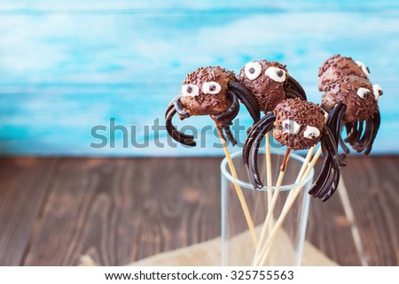 Homemade Halloween chocolate spider cake pops in a glass on wooden background - stock photo